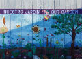 "Mural with plants, birds and butterflies reading ""Nuestro Jardín/Our Garden."""