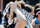 Woman putting keffiyeh on.  Photo by Alma del Pueblo.