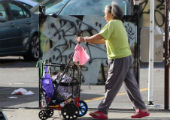 Woman pushing shopping cart on Oakland street.